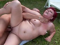 Redhead granny Eszmeralda sucks and rides a cock in the garden