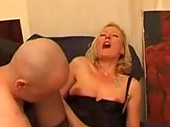 Mature blonde in black lingerie gives a blowjob