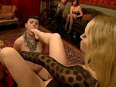 Two chained babes are being fucked by a bitch in a strapon