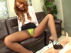 Long-haired Japanese cutie gives a stunning footjob to her man