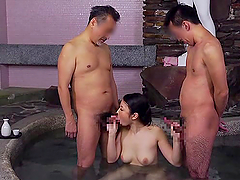 Japanese hottie enjoys sucking two dicks in an indoor pool