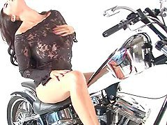 Big tittied Tera Patrick poses on camera near the motorbike